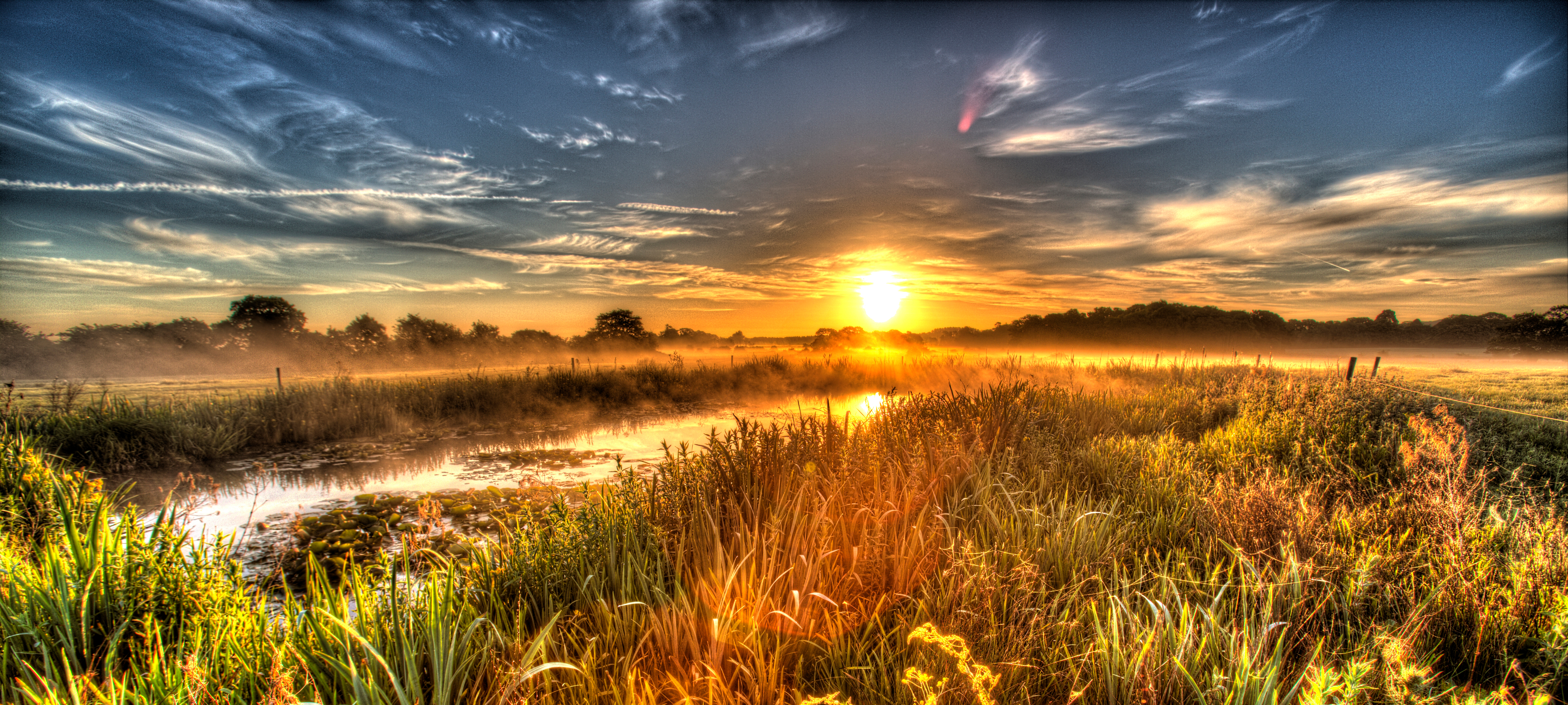 Artistic sunrise view of a freshwater pond in a Cheshire farming field.