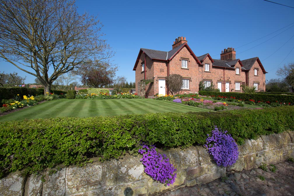 Village of Aldford, England. Picturesque spring view of an Eaton Estate managed house on Aldford's School Lane. Many of Alford village houses and farm buildings are owned by the Duke of Westminster's Eaton Estate.