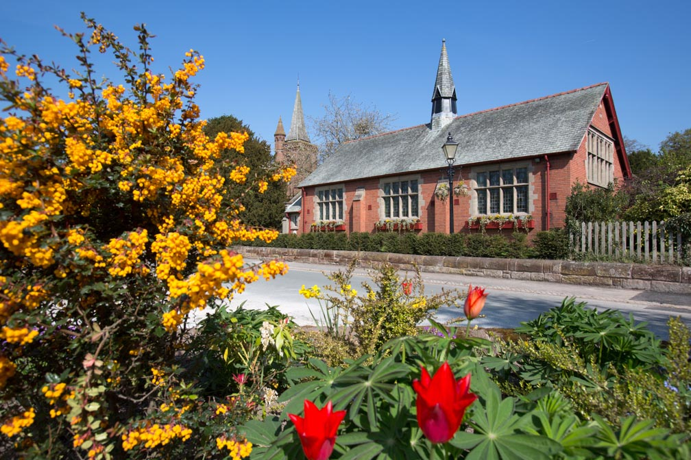 Village of Aldford, England. Picturesque spring view of Aldford Village Hall in Church Lane.