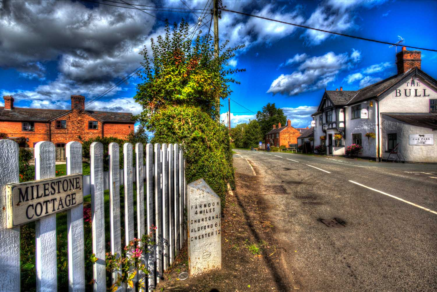 Village of Shocklach, Cheshire, England. Artistic view of the B5069 main road through the village of Shocklach, with The Bull Inn public house in the background.