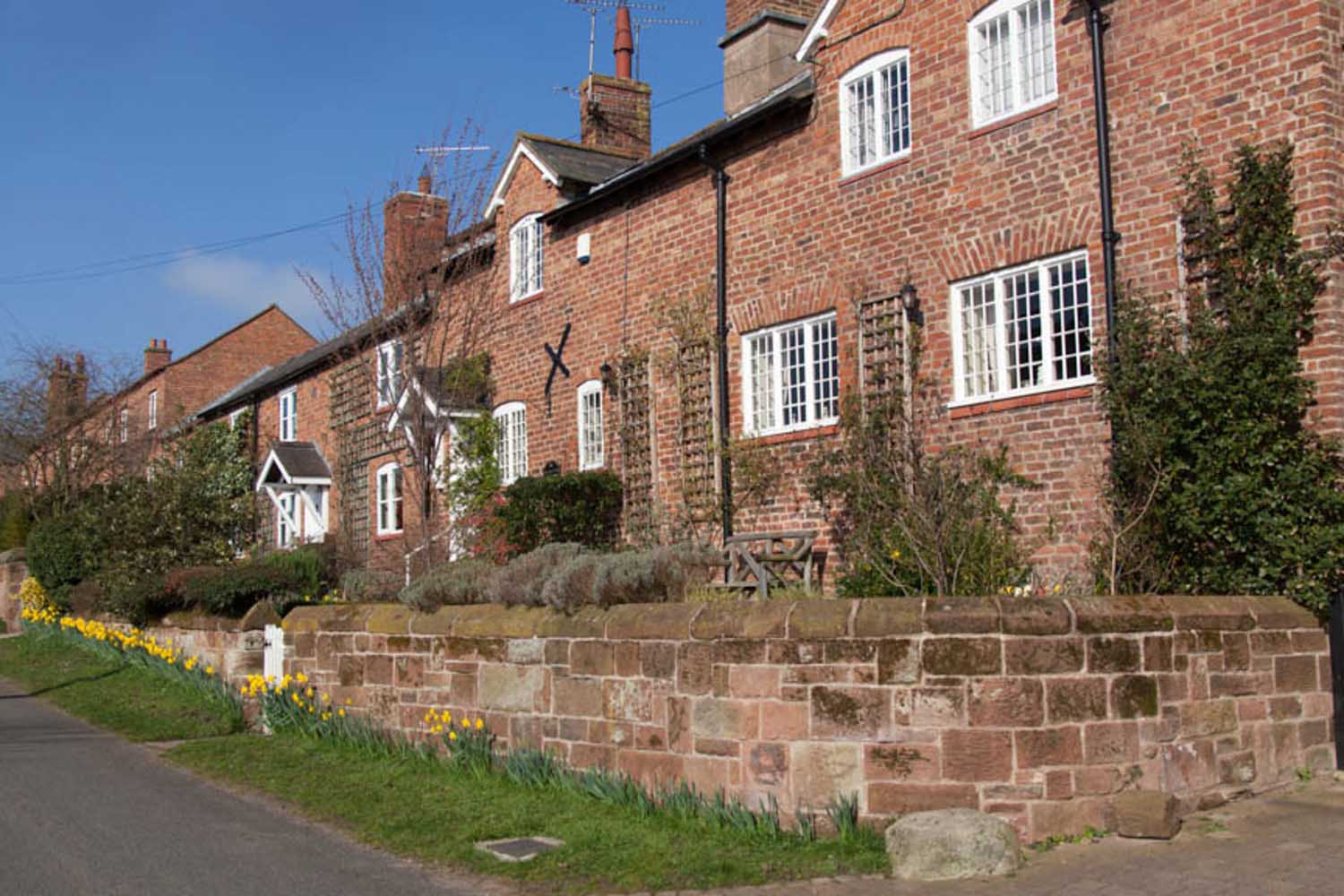 Village of Churton, Cheshire, England. Picturesque spring view of houses on Churton's Pump Lane.