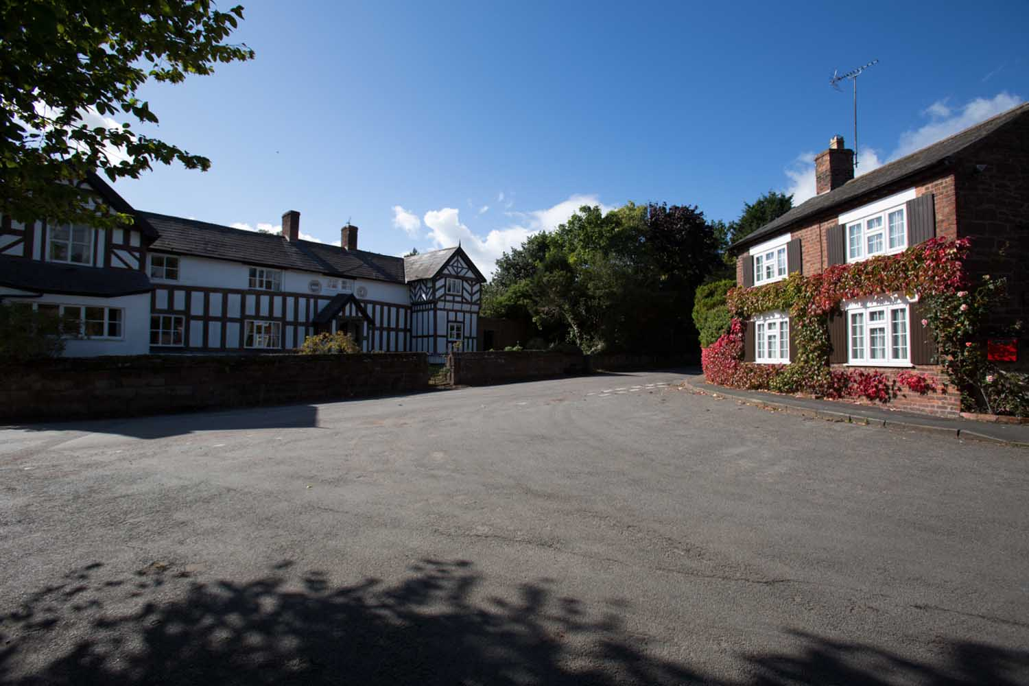 Village of Churton, Cheshire, England. Picturesque view of Churton's Pump Lane with the Grade II listed Churton Hall on the right of the image.