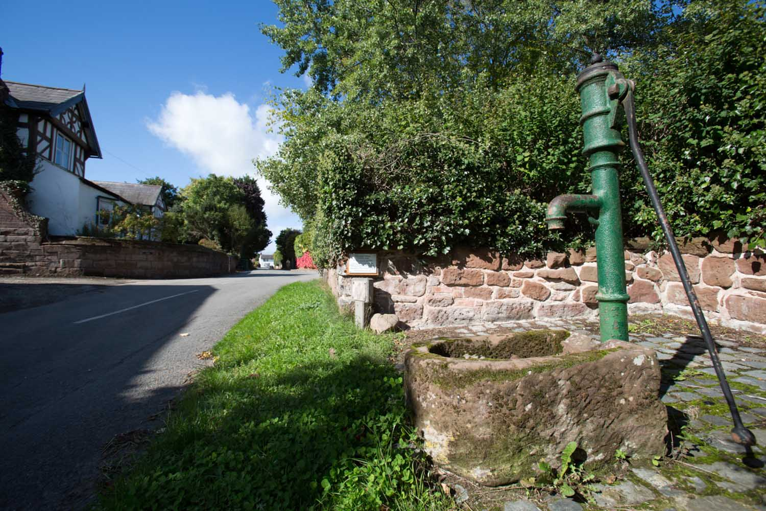 Village of Churton, Cheshire, England. Picturesque view of a restored water pump on Pump Lane.