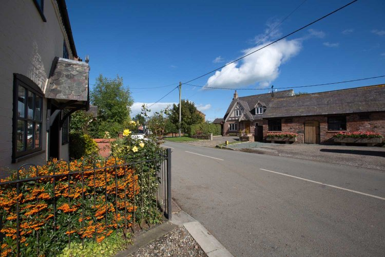Village of Shocklach, Cheshire, England. Picturesque view of the B5069 main road through the village of Shocklach. An old Cheshire County Council milestone is in the foreground, with 'The Bull Inn' public house in the background.